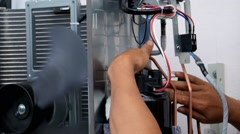 Young worker sets split system air conditioner outdoor Stock Footage