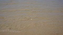 Sea tide washes up a sandy shore and out again - stock footage