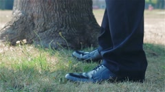 Businessman with Formal shoes standing on grass. - stock footage