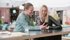 Happy female friends using cell phone at sidewalk cafe  HD Stock Footage