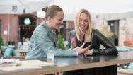 Stock Video Footage of Happy female friends using cell phone at sidewalk cafe  HD