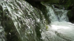 Two small waterfall flowing into a small vir Stock Footage
