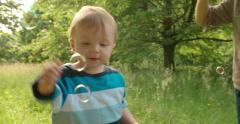 Brothers Play With Bubbles, outside in the park Stock Footage