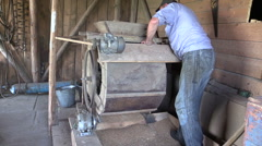 Farmer processed grain with old hand cleansing harp in barn Stock Footage