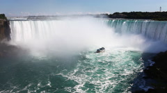 Stock Video Footage of Below Niagara Falls with a tour boat in the spray