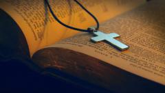 Silver cross & holy bible in candle light Stock Footage