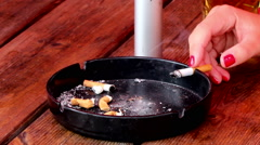Woman's hand puts a smoldering cigarette in ashtray. - stock footage