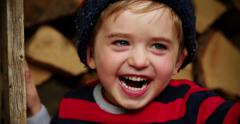 Young Boy Playing Peekaboo at Logs Stock Footage