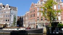 Canal houses, house boat and graffiti art in Amsterdam Stock Footage