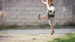 Young boy doing kick with ball on natural street Stock Footage