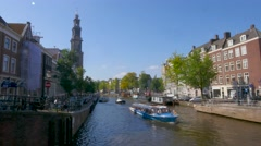 Amsterdam canal with canal boat and church, Westerkerk - stock footage
