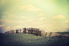 Sunny day in countryside. summer landscape with old broken fence at pasture   Stock Photos