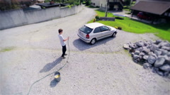 Aerial footage of young man spraying car with water Stock Footage