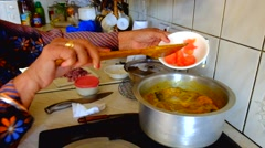 Indian cook adding indgredients to cooking pot & stirring with wooden spoon Stock Footage