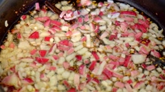 Chopped red onions, garlic and spices frying in a pan Stock Footage