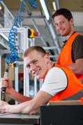 Man controlling assembly process at factory Stock Photos