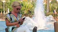 Woman sitting on the park bench and sending text  Message Stock Footage