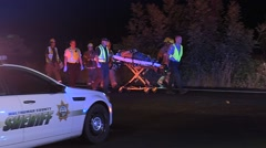 Fire And Medical Transporting Patient To An Ambulance After A Car Crash - stock footage