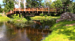 old bridge over fast flowing river and girl in suuny day park - stock footage