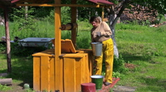 Woman scoop water from rural yellow painted well in bucket Stock Footage