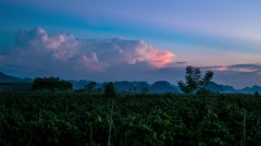 Sunset clouds over hills and farming fields and darking sky.7s Stock Footage