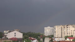 Rainbow on sky, rainy day outside, rainbow colors view, dark clouds above city Stock Footage