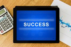 Stock Illustration of success word on digital tablet