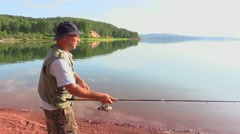 Man is fishing by spinning Stock Footage