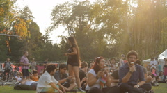 Crowd Of People Sitting On Grass In A Park Enjoying A Summer Festival Front Shot Stock Footage