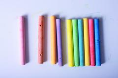 Rainbow colored chalk arranged on a white background, chalk isolated Stock Photos