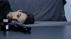 Young Man Laying In A Couch With Suicidal Thoughts, Gun, Pills, Booze, Pan Stock Footage