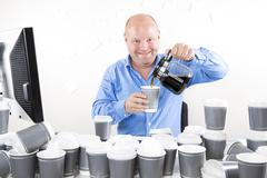 Happy office worker drinks too much coffee Stock Photos