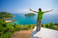 Man on tropical island cliff with small beach below Stock Photos
