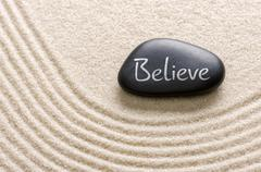 Stock Photo of black stone with the inscription believe