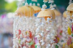 Stand with sea shells on thin strings souvenirs at small road shop in asia Stock Photos