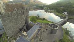Flying over Eilean Donan Castle in Scotland on a summer morning Stock Footage
