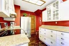 white kitchen room with contrast bright red walls - stock photo