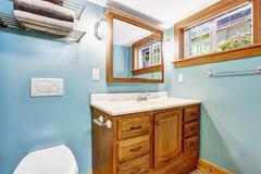 Blue bathroom interior with wooden vanity cabinet Stock Photos