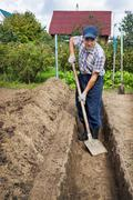 Man digging the earth to build a deep bed of Stock Photos
