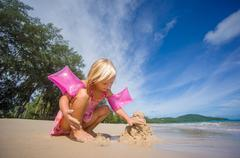 adorable girl in pink swimming suit and inflatable arm bands build sand tower - stock photo