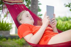 young woman reading on electronic tablet reader relaxing in hammock under pal - stock photo