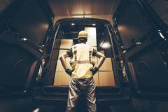 Cargo van delivery. rear cargo doors reloading. construction guy talking care Stock Photos