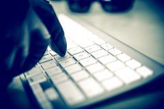 hacker in work. hacker hand in black glove typing on the keyboard. closeup ph - stock photo