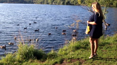 woman on the edge of the pond feeding the ducks floating - stock footage