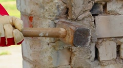 Man with sledge-hammer destroying old wall Stock Footage