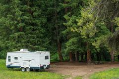 Boondocking dry camping in the forest. small travel trailer with solar panels Stock Photos