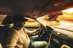 Stock Photo of fast driving car interior wide angle photography. young men after his 30 driv