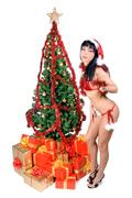 Mrs. Claus with gift boxes under Christmas tree Stock Photos