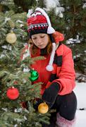 Girl decorate christmas tree in winter nature Stock Photos