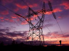 sunset with high-voltage lines on the mast - stock photo